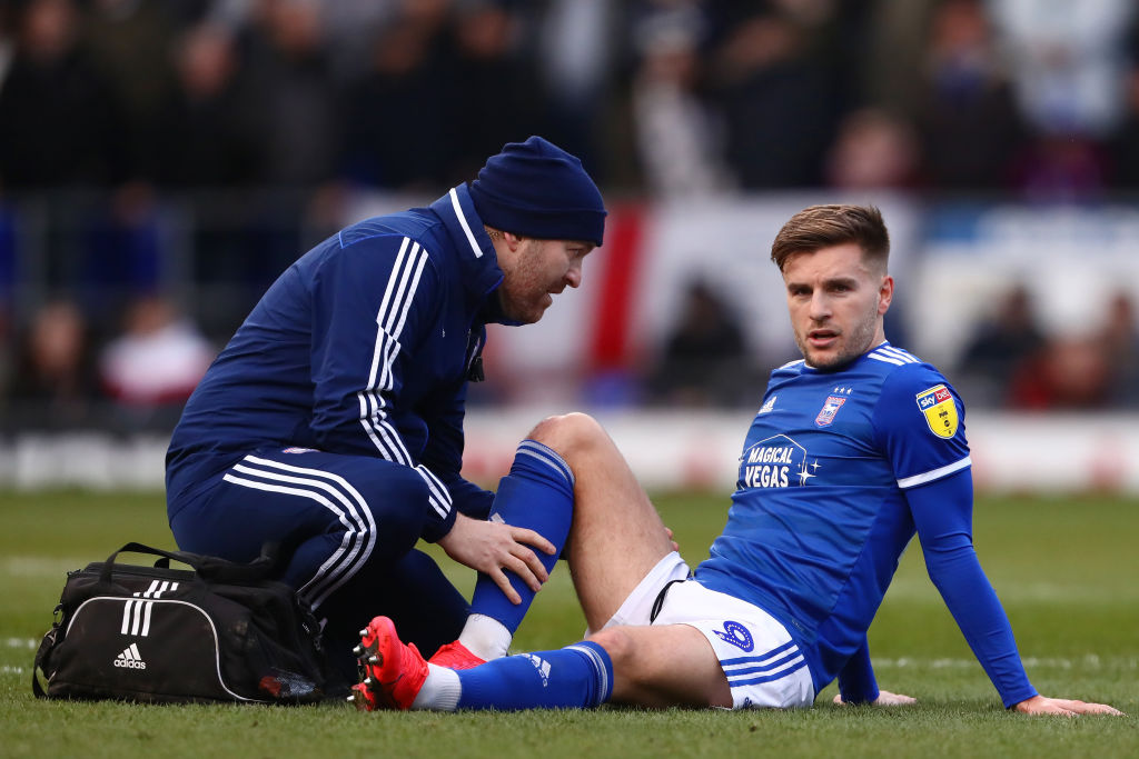 Luke Garbutt of Ipswich Town receives treatment before being...